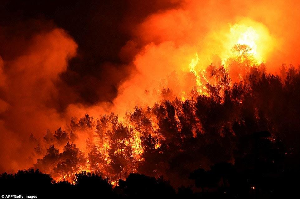 Um fogo arde em Les Pennes-Mirabeau, perto de Marselha.  Incitou por fortes ventos, o fogo pegou e se espalhou mais de 5.600 acres de mato, grama e algumas áreas arborizadas