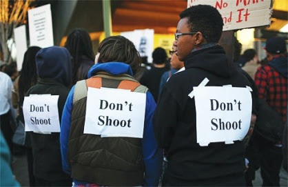 """Three (pink) Protestors at Oscar Grant Rally have signs taped to their backs that say """"Don't Shoot"""""""
