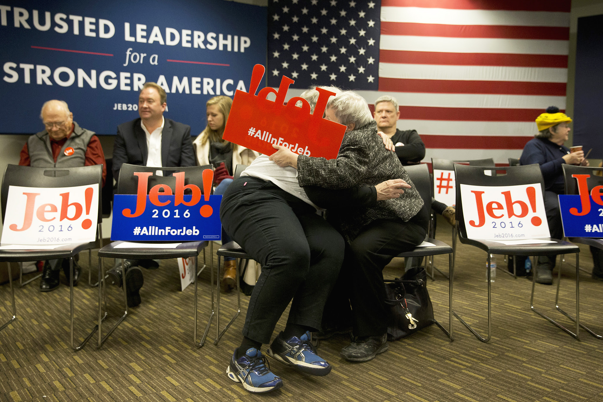 Jan Patterson, Joni Scotter...Jan Patterson, center left, hugs her friend Joni Scotter before the start of a town hall meeting with Republican presidential candidate, former Florida Gov. Jeb Bush, Tuesday, Jan. 12, 2016, in Coralville, Iowa. (AP Photo/Jae C. Hong)
