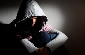 Young person in a dark corner