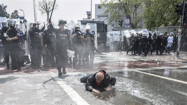 En Turquie, un manifestant qui s'est retrouvé au sol après avoir été renversé par le jet d'un canon à eau tente de se relever sous le regard des policiers anti-émeutes.