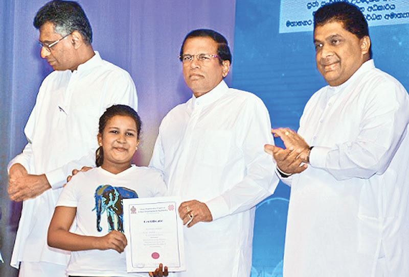 Ridma Seriya, a program to mark the World Children's Day with art and aesthetic performances of the children living in flats in Colombo was held at the BMICH under the auspices of President Maithripala Sirisena yesterday.A child receiving her certificate from the President. Western Province Development and Megalopolis Minister Patali Champika Ranawaka and Deputy Media Minister Lasantha Alagiyawanna look on. Picture by Sudath Malaweera.
