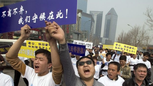 Chinese relatives of passengers onboard the missing Malaysia Airlines plane, flight MH370, shout in protest as they march towards the Malaysia embassy in Beijing, China, Tuesday, March 25, 2014
