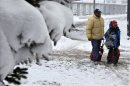 People walk in the snow at Buffalo Niagara International Airport in Buffalo, N.Y., Saturday, Dec. 29, 2012. A mild but widespread winter storm has developed over the Northeast and the upper Ohio River Valley, the second in less than a week for the regions. (AP Photo/Mel Evans)