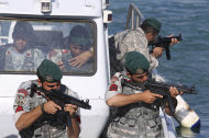 Iranian navy members take positions during a drill in the Sea of Oman, Wednesday, Dec. 28, 2011. Iran's navy chief warned Wednesday that his country can easily close the strategic Strait of Hormuz at the mouth of the Persian Gulf, the passageway through which a sixth of the world's oil flows. The navy is in the midst of a 10-day drill in international waters near the strategic oil route. (AP Photo/IIPA,Ali Mohammadi)