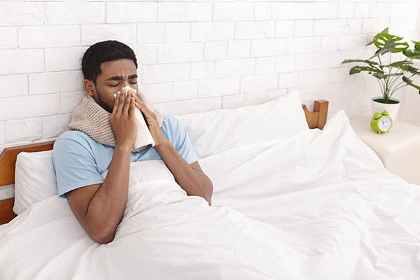 Man in bed blowing nose