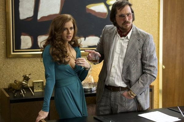 Amy Adams and Christian Bale play two con artists in AMERICAN HUSTLE.