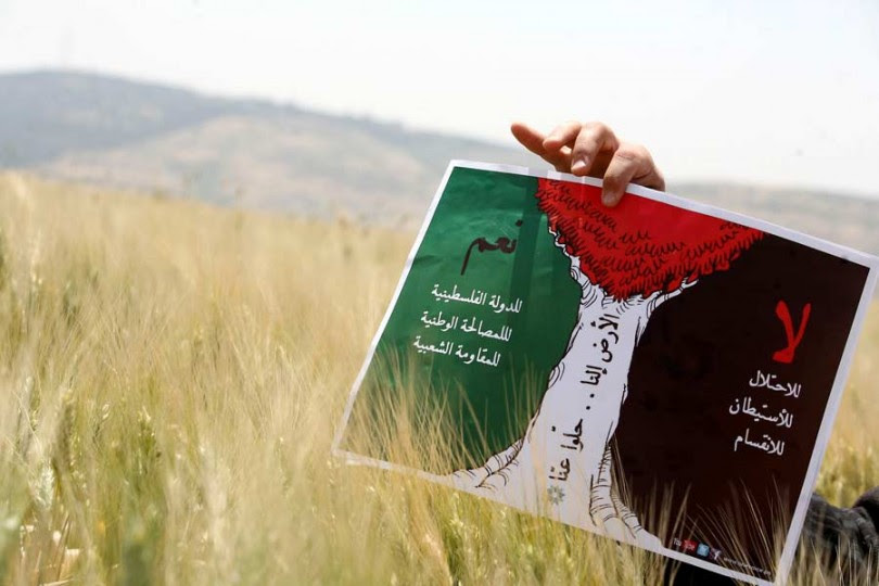 A protester holds a poster reading 'No to occupation, settlements and division. Yes to a Palestinian state, national unity and popular resistance.' during a rally held by Palestinian and foreign peace activists to mark the 10th anniversary of the Arab Peace Initiative, seeking to end Israeli occupation and establish an independent Palestinian state, in the West Bank village of Faquaa near Jenin on April 28, 2012. AFP PHOTO/SAIF DAHLAH (Photo credit should read SAIF DAHLAH/AFP/GettyImages)