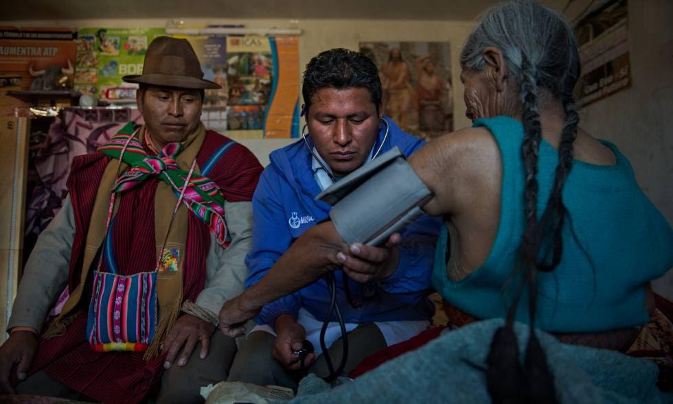 Un médico académico toma la presión a una paciente en la comunidad de Sica Sica, Bolivia.