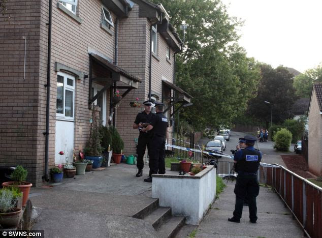 Search: Police outside the Paignton home of Katharine Hooper where the body of a two-year-old boy was found