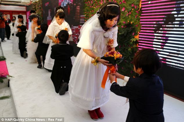 On bended knee: The grooms kneel to hand their brides a bouquet during the ceremony