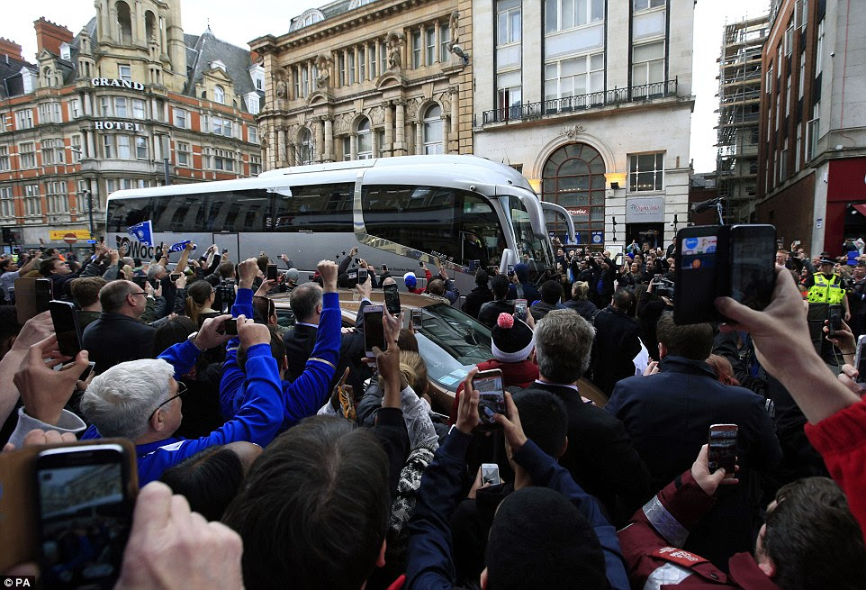 The Leicester team bus arrives at the pizza restaurant in Leicester this afternoon as fans scramble to take a picture of the moment