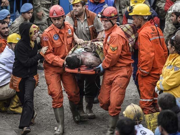 Equipe de resgate carrega nesta quarta (12) corpo de homem morto em acidente em mina de Sana  (Foto: AFP PHOTO/Bulente Kilic)