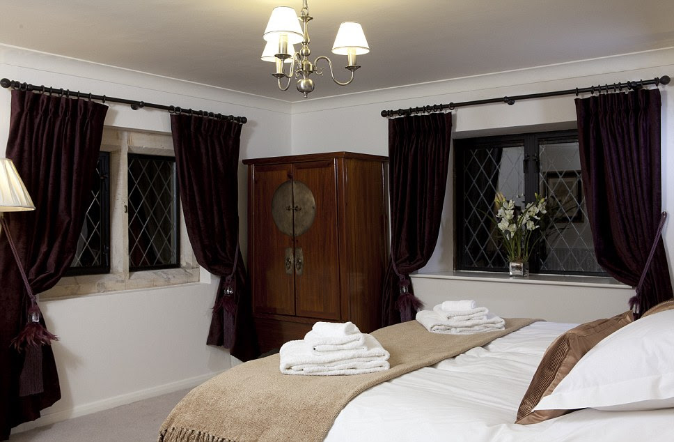 With purple curtains and a period piece wardrobe in the corner the main bedroom at Bath Lodge Castle looks fit for royalty