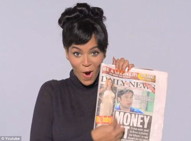 Olha, sou eu!  Segurando um exemplar do The New York Daily News, Beyonce aponta para uma imagem do tapete vermelho de si mesma na capa, em que sua barriga está em exposição em um longo vestido elegante