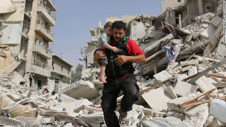 A Syrian man carries a baby after removing him from the rubble of a destroyed building.