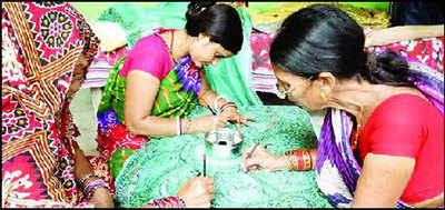 Women painting a silk saree at a village in Madhubani.