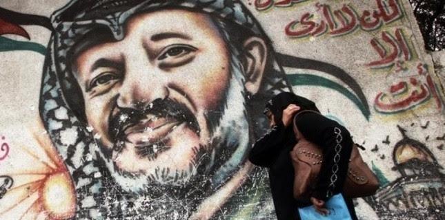 Portrait de Yasser Arafat dans une rue de Gaza. Des examens conduits par un laboratoire suisse ont révélé des traces anormalement élevées de polonium, un élément chimique radioactif, dans les effets personnels de l'ancien dirigeant palestinien, décédé à l'hôpital militaire de Percy en France en 2004. /Photo d'archives/REUTERS/Suhaib Salem (c) Reuters