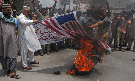 Pakistani protesters burn a representation of an American flag