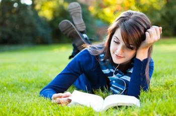 College student reading, lying outside on grass