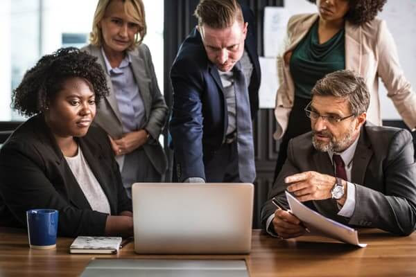 Recruiter at computer showing top executive candidates to management team