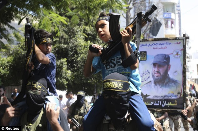 Indoctrinated: Two young Palestinian boys are seen perched on the shoulders of Islamic Jihad militants, holding weapons in their hands during the victory rally in Gaza City