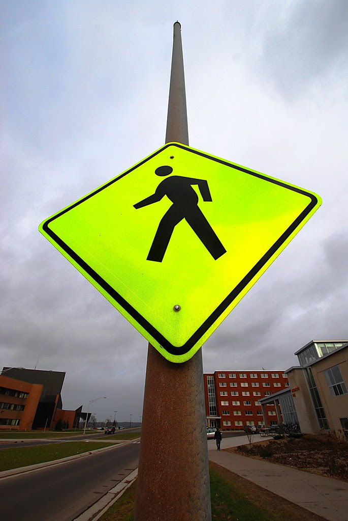 A bright yellow crosswalk sign, on a pole.
