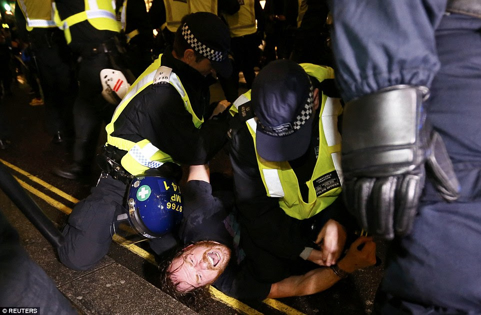 A man struggles as he is detained by police officers in central London after violent clashes erupted during the demonstrations