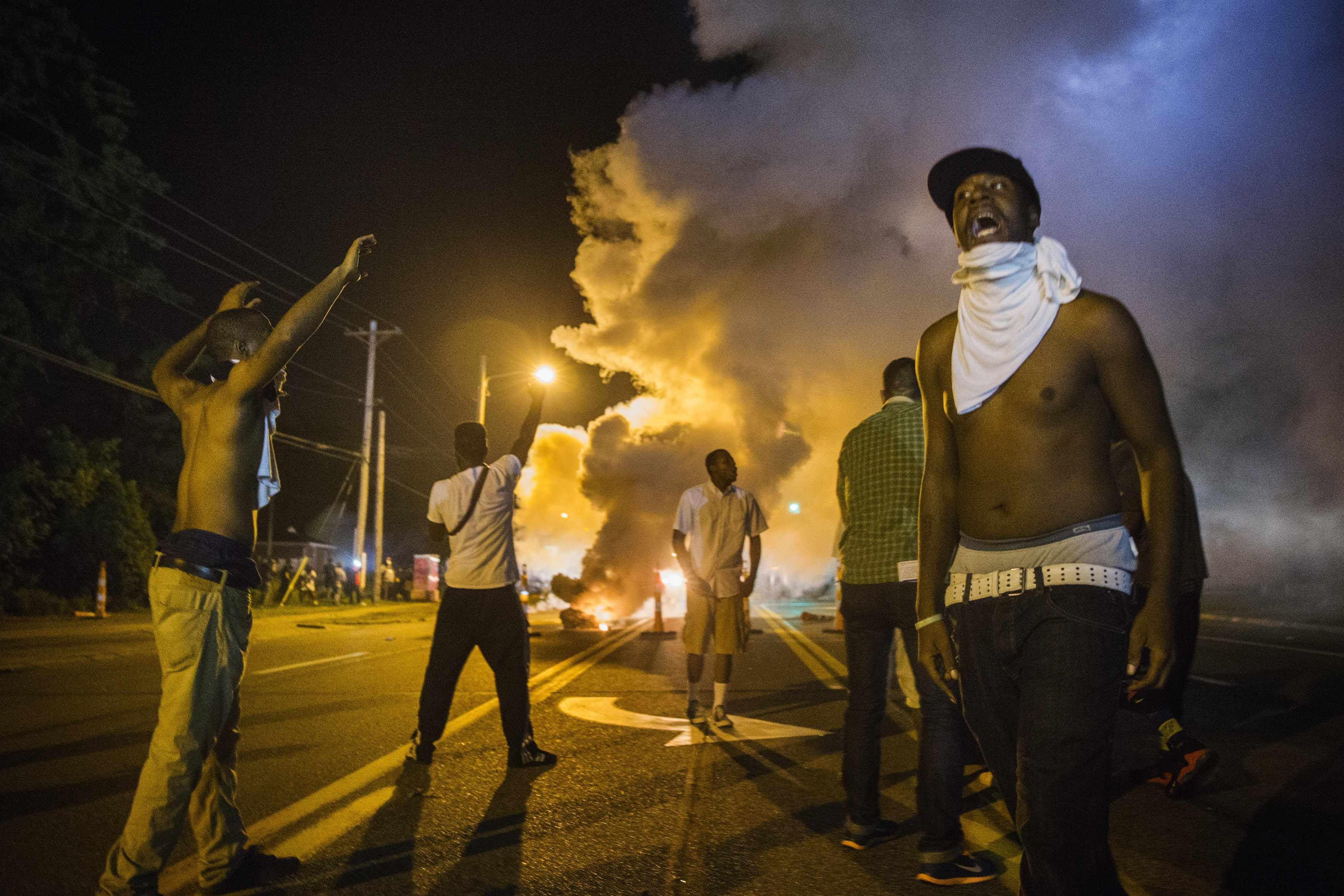 Demonstrators in Ferguson react to tear gas fired by police on Aug. 18 during protests over the fatal shooting of teenager Michael Brown. (REUTERS/Lucas Jackson)