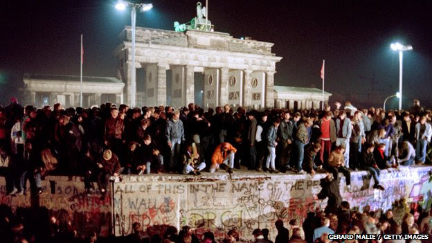 Thousands of young East Berliners crowd atop the Berlin Wall, near the Brandenburg Gate, on November 11, 1989
