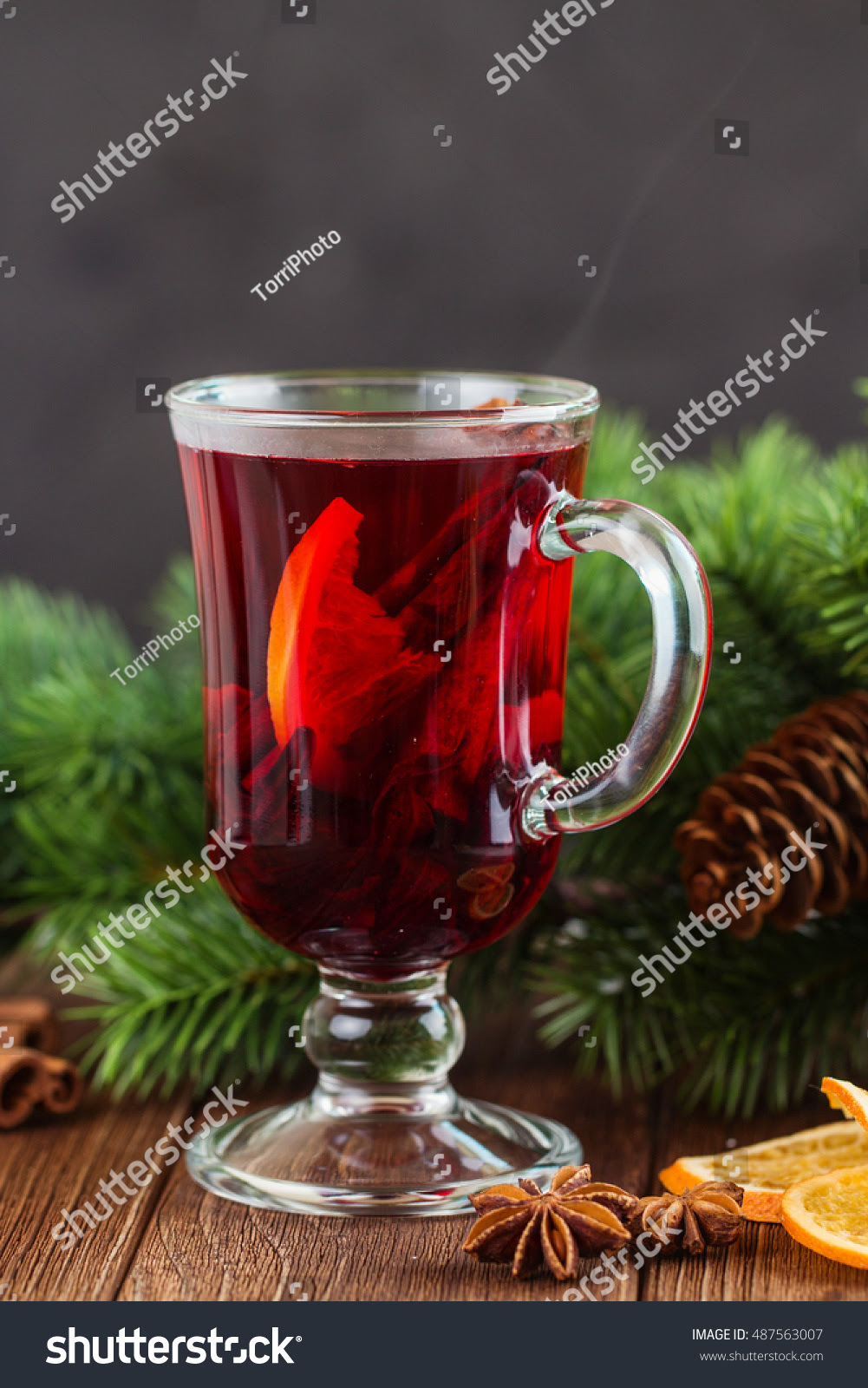 Mulled wine with spices on Christmas rustic background with fir branch