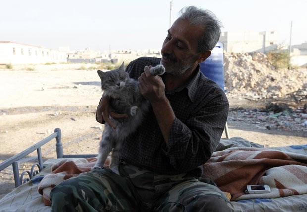 Rebelde sírio brinca com gato próximo ao aeroporto militar de Nairab, em Aleppo, em 1º de outubro (Foto: Reuters)