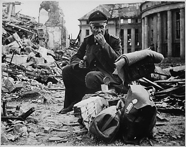 Nazi officer eating a can of C-rations in the ruins of Saarbrucken