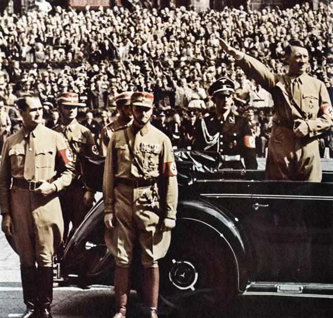 Deputy Führer Rudolf Hess (left) and brownshirt chief of staff Victor Lutze watch SS troops marching by as Adolf Hitler gives the Nazi salute from his Mercedes-Benz 770K, Nuremberg, 1938.
