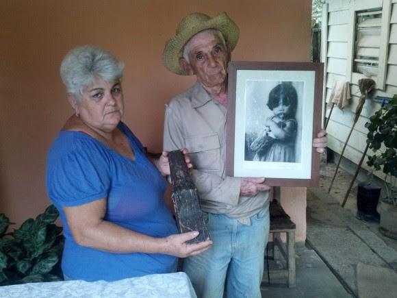 Aracelys y Nicolás muestran el pedazo de madera original que portaba Paula y la foto firmada por Korda. Foto: Eduardo González Martínez.