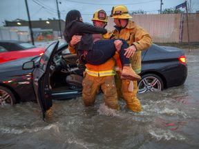 A firefighter carries a woman from her car after it was caught in street flooding as a powerful storm moves across Southern California