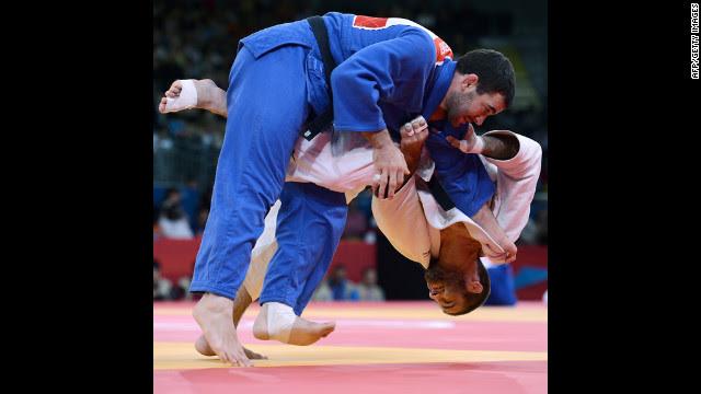 Travis Stevens, in white, of the United States tries to take down Slovenia's Aljaz Sedej during the men's under 81-kilogram judo contest match Tuesday.