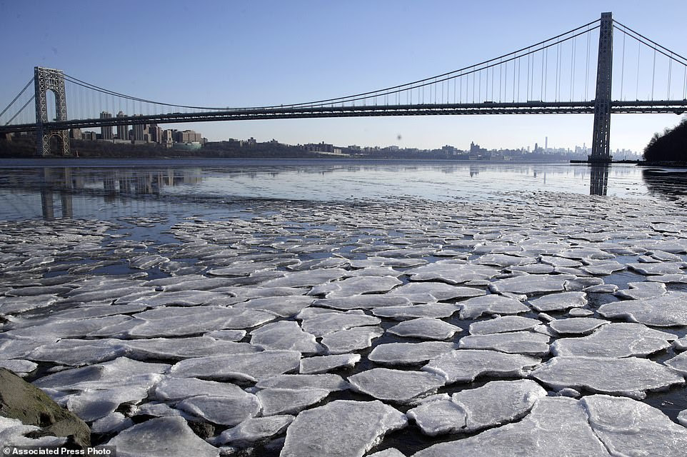 A layer of ice is broken into pieces floating along the banks of the Hudson River at the Palisades Interstate Park with the George Washington Bridge in the background, Tuesday, Jan. 2, 2018, in Fort Lee, N.J.A new study of the brutal American cold snap found that the Arctic blast really wasn't global warming but a freak of nature.
