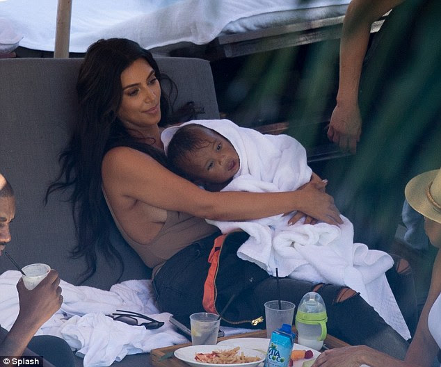Mom's the word: Worried about him feeling the chill, Kim wrapped Saint in a fluffy white towel