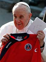 Pope Francis holds up a jersey and notes that were presented to him during a March 2015 visit to a parish outside Rome. CNS Photo/Paul Haring