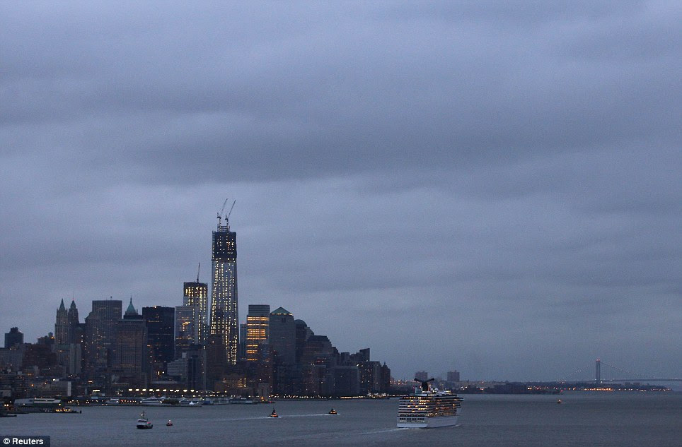 On alert: Gray skies hover over the skyline of New York's Lower Manhattan as millions of residents prepare for Hurricane Sandy, which could become the largest storm to hit the United States