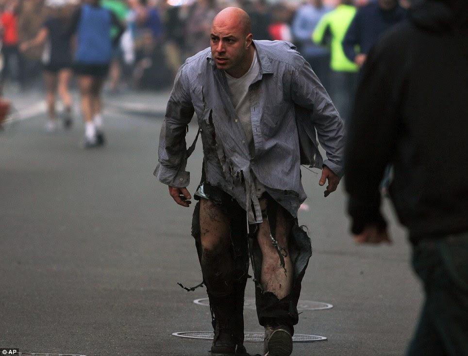 Walking Wounded: A man staggers away from the scene of the explosions at the 2013 Boston Marathon in Boston, today