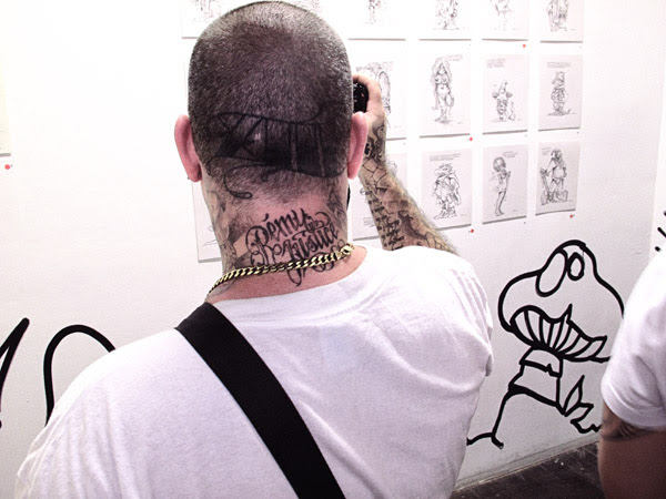 Mark Bode exhibition at China Heights gallery, man with tattoo on neck photographing orginal drawings by Mark.