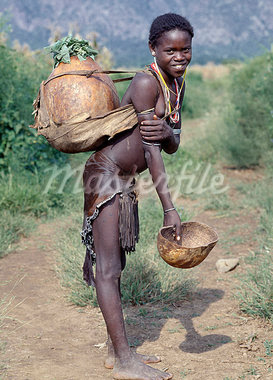 A girl of the Tsemay tribe of remote Southwest Ethiopia wears an attractively decorated leather skirt and apron. She is returning home with water in the large gourd carried on her back. The Tsemay are a small tribe neighbouring the more numerous Hamar people with whom they share a common language. Stock Photo - Rights-Managed, Artist: AWL Images, Code: 862-03354111