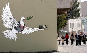 Una paloma de la paz con chaleco antibalas y un visor de un francotirador dibujado sobre su pecho en la ciudad de Belén, Cisjordania. (Foto: EFE)