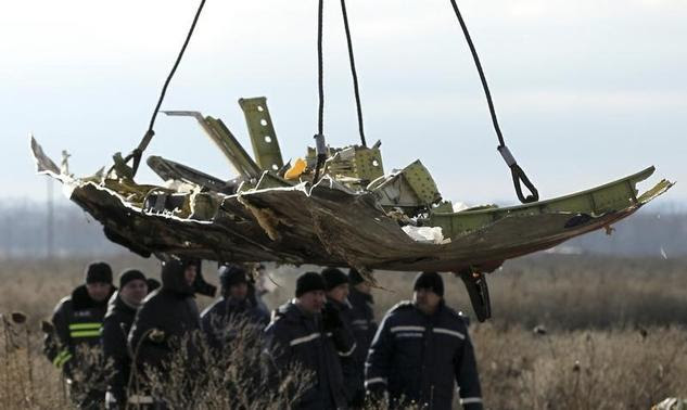 A crane transports a piece of the Malaysia Airlines flight MH17 wreckage at the site of the plane crash near the village of Hrabove (Grabovo) in Donetsk region, eastern Ukraine November 20, 2014. REUTERS-Antonio Bronic