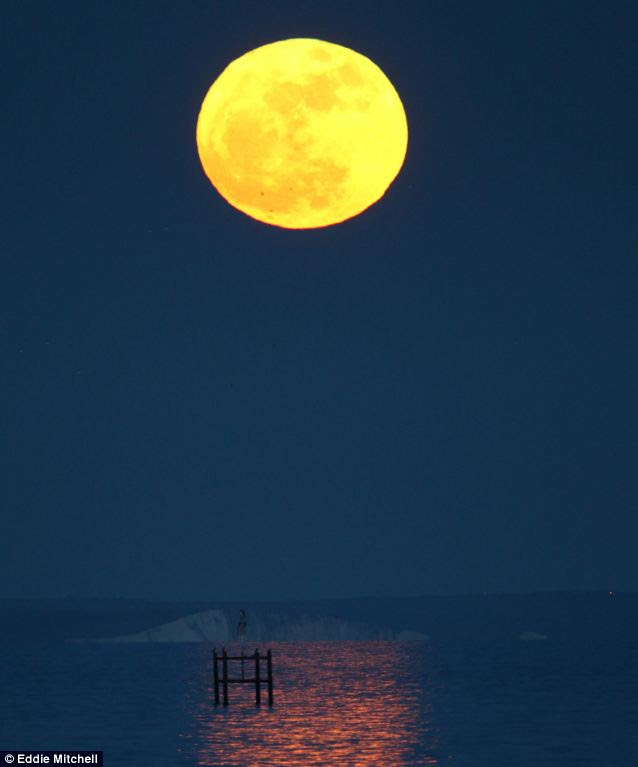 The moon as seen from the end of Worthing Pier in Sussex, looking east towards Beachy Head
