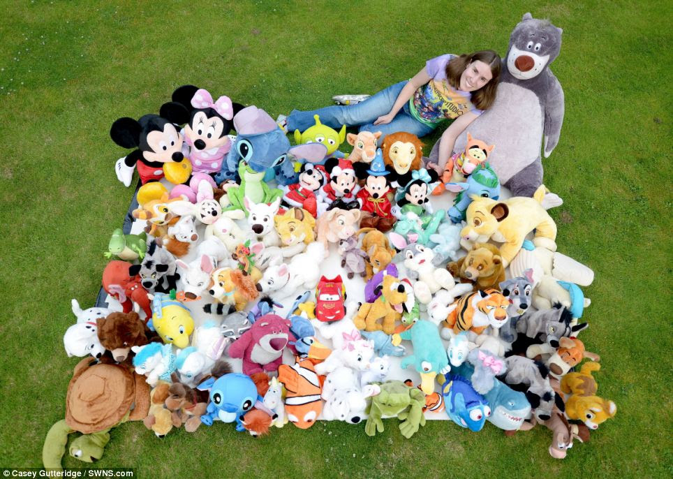 Happy family: Mrs Rayner rests against a 4ft cuddly model of the Jungle Book character Baloo as she shows off her collection