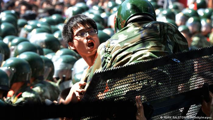 A man tries to climb over police lines during an anti-Japanese protest over the Diaoyu islands issue, known as the Senkaku islands in Japanese, outside the Japanese Embassy in Beijing on September 15, 2012.