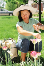 Photo: Woman in garden using insect repellent